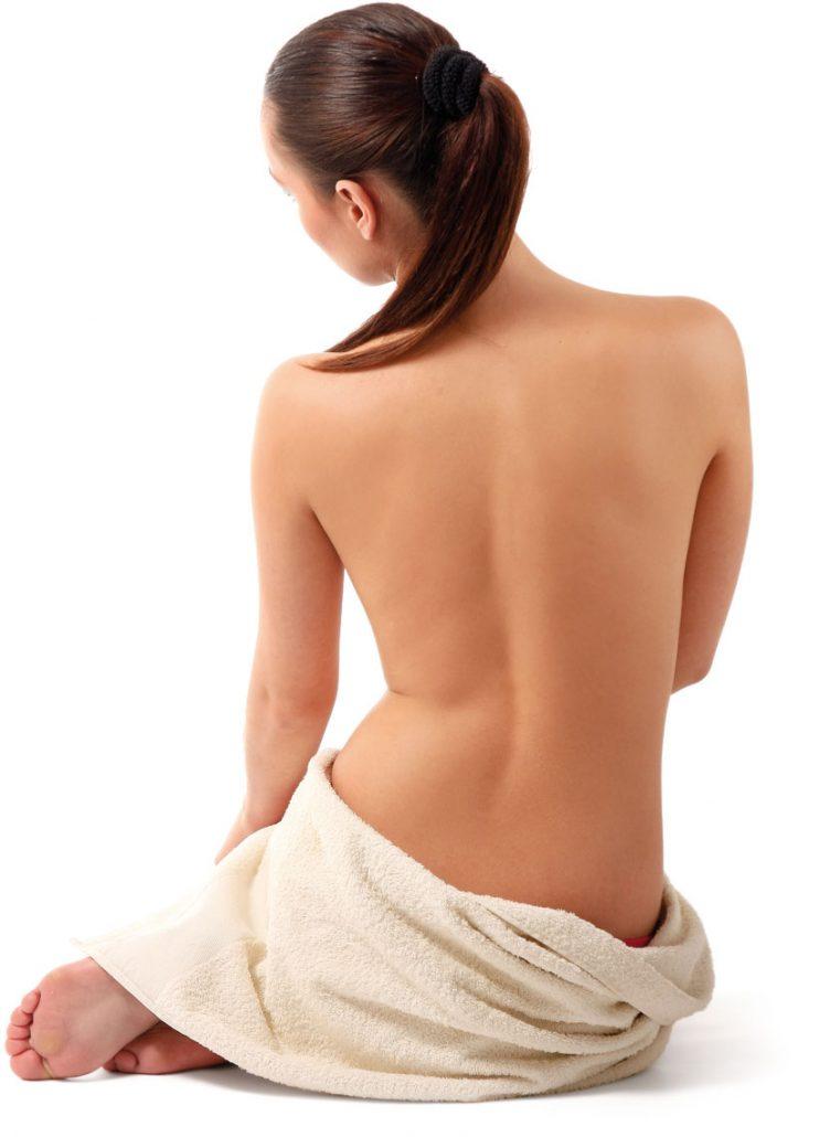 Frau von hinten mit beigen Handtuch bedeckt ihren Unterkörper, zeigt aber ihren Rücken.