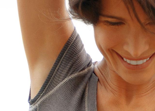 Frau mit einem grauen Pullover streckt ihren rechten Arm in die Höhe und zeigt ihre glatt rasierte Achsel