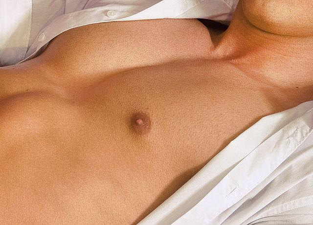 Mann mit geöffneten weißem Hemd und glatt rasierter Brust
