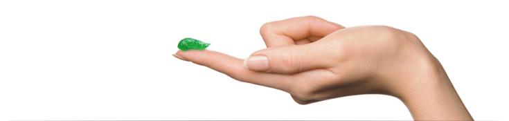 Frau streckt ihren Zeigefinger aus, auf dem ein grüner Streifen ilon Salbe classic präsentiert wird